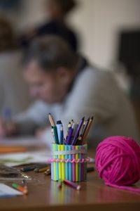 W tle osoba starsza podczas terapii zajęciowej