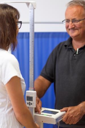 Lekarz ważacy kobietę na wadze medycznej