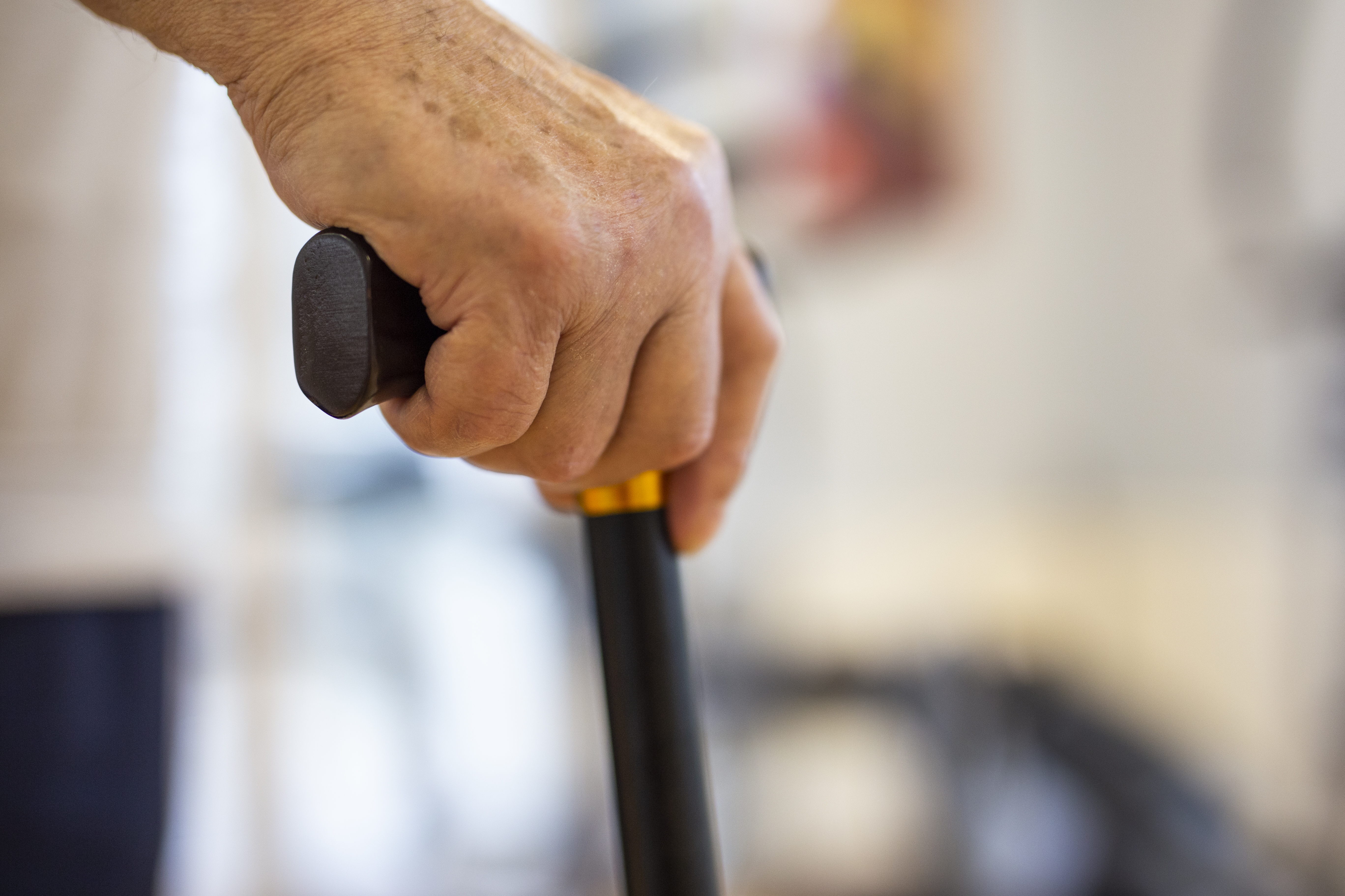 Ręka starszej osoby trzymająca laskę